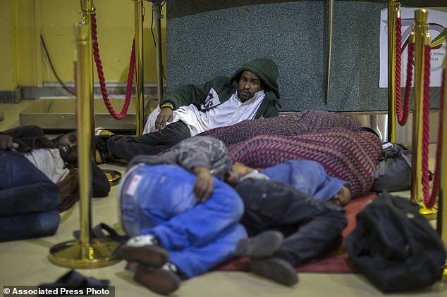 In this photo taken Friday, Dec. 22, 2017, Ethiopian migrants sleep on cold floors after being deported from Saudi Arabia, at the airport in Addis Ababa, Ethiopia. Undocumented Ethiopian migrants who are being forcibly deported from Saudi Arabia by the thousands in a new crackdown say they were mistreated by authorities while detained. (AP Photo/Mulugeta Ayene)