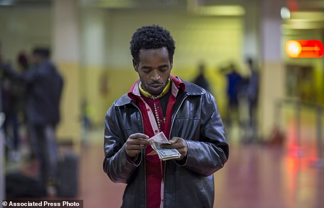 In this photo taken Friday, Dec. 22, 2017, Ethiopian Hassen Yusuf counts the only money he managed to bring home, equivalent to about US$50, after being deported from Saudi Arabia, at the airport in Addis Ababa, Ethiopia. Undocumented Ethiopian migrants who are being forcibly deported from Saudi Arabia by the thousands in a new crackdown say they were mistreated by authorities while detained. (AP Photo/Mulugeta Ayene)