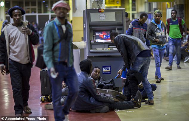 In this photo taken Friday, Dec. 22, 2017, Ethiopian migrants lie on the floor upon their arrival after being deported from Saudi Arabia, at the airport in Addis Ababa, Ethiopia. Undocumented Ethiopian migrants who are being forcibly deported from Saudi Arabia by the thousands in a new crackdown say they were mistreated by authorities while detained. (AP Photo/Mulugeta Ayene)