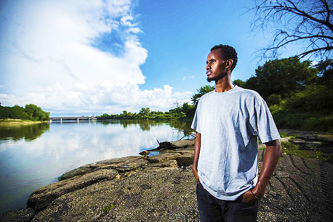 Yahya Samatar, refugee claimant from Somalia who swam across the Red River to get to Canada, stands by the river in Winnipeg on Friday, Aug. 7, 2015.    Mikaela MacKenzie / Winnipeg Free Press