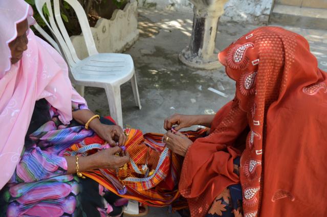 Elderly Somali ladies finalizing on a garment before the wedding