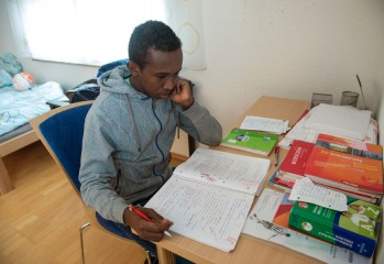Nasri Sugal Jaamac aus Somalia sitzt am 26.03.2015 in Stuttgart (Baden-Württemberg) im seinem Zimmer in der Wohngruppe des Jugendamtes an seinem Schreibtisch, auf dem Lernmaterialien liegen. Jaamac floh aus Somalia und kam, weil er noch nicht volljährig ist, in ein Wohnheim des Jugendschutzes. Foto: Marijan Murat/dpa (zu dpa «Auf der Flucht: Ein 16-jähriger Somali landet in Stuttgart» vom 29.03.2015)